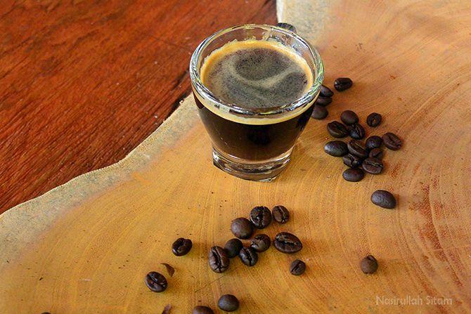 Secangkir kopi dengan biji kopi yang berserakan