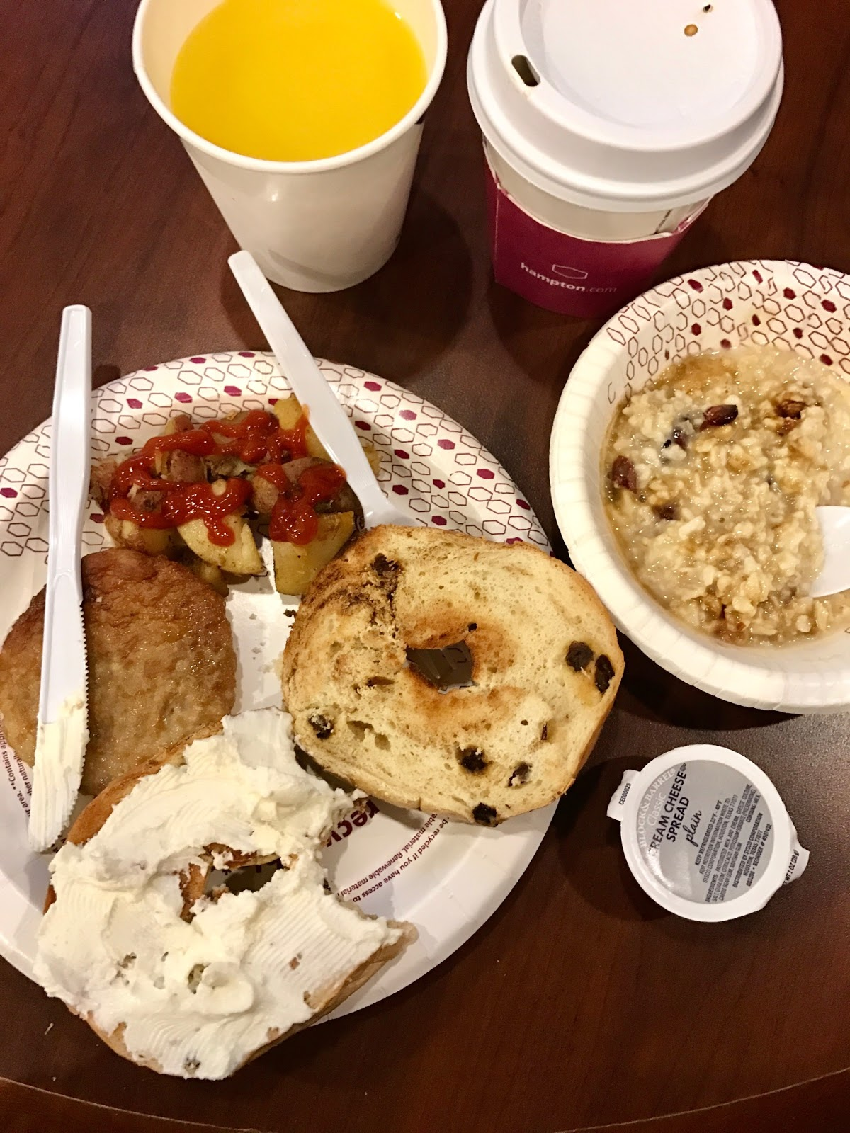 continental breakfast including oatmeal, bagel with cream cheese, sausage and orange juice.