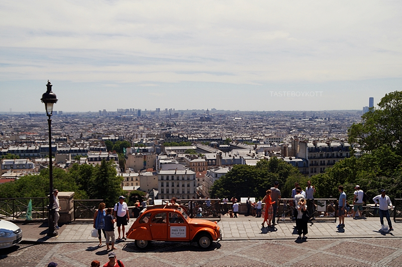 Ausblick von der Sacre Coeur auf Paris im Sommer mit orangem Oldtimer | Tasteboykott