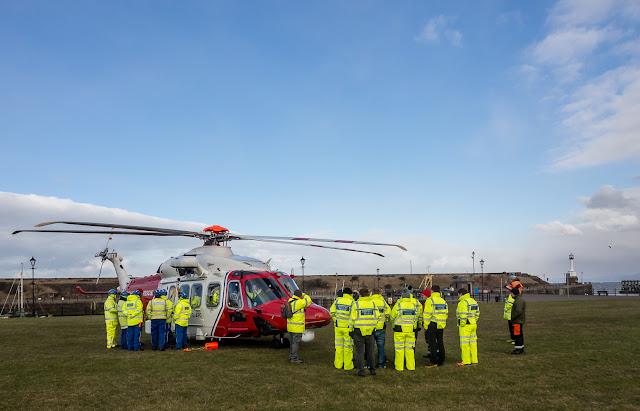 Photo of lifeboat and Coastguard rescue teams with the Coastguard helicopter