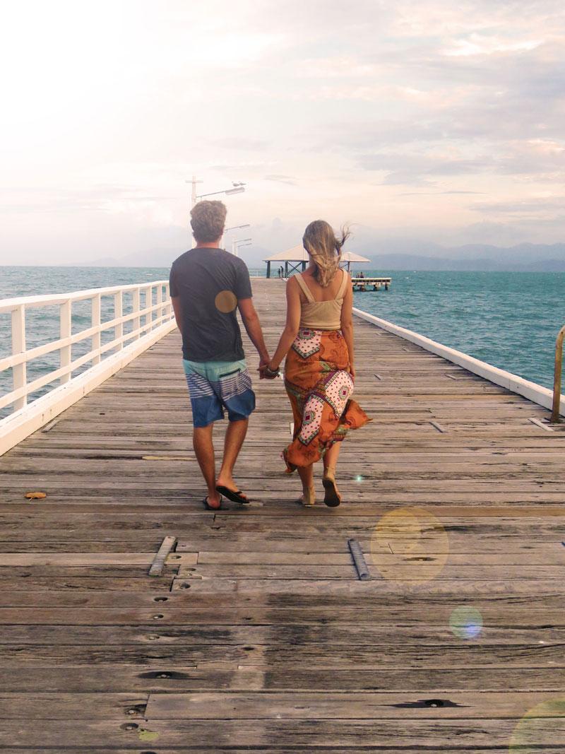 couple walking along pier hand in hand