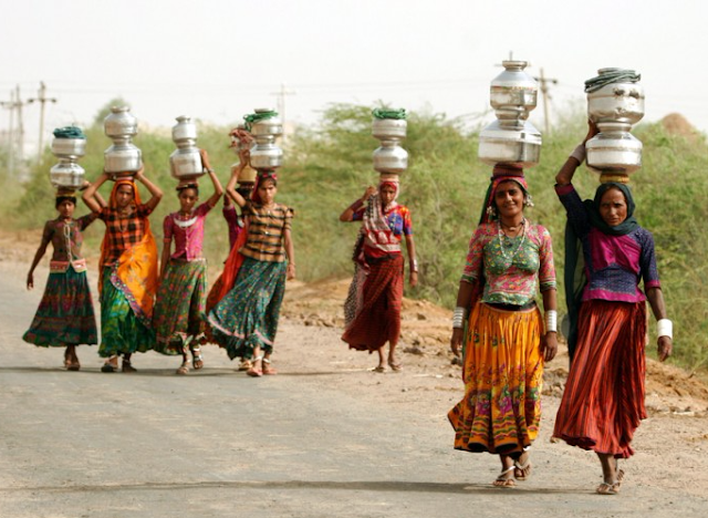 Women carry jugs of water in India