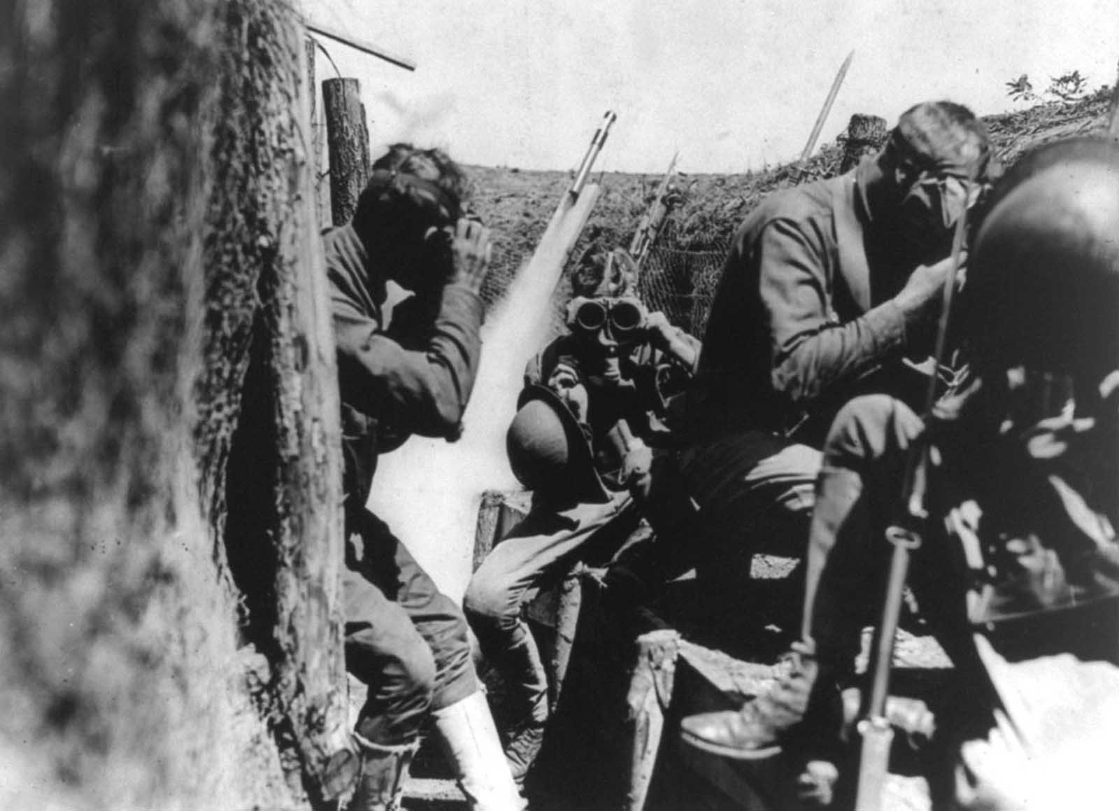 U.S. soldiers in trench putting on gas masks. Behind them, a signal rocket appears to be in mid-launch. When gas attacks were detected, alarms used included gongs and signal rockets.