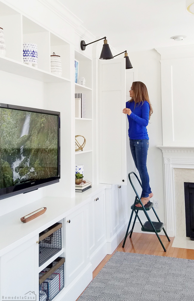 how to build entertainment center and storage space - Cristina Garay organizing the shelves