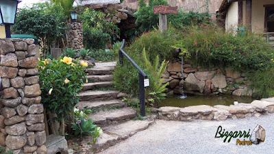 Escada de pedra com pedra moledo tipo chapa com cantos. Escada com pedra com junta de grama com o corrimão de madeira, o lago ornamental com pedra e os pilares de pedra para o lampião no jardim.