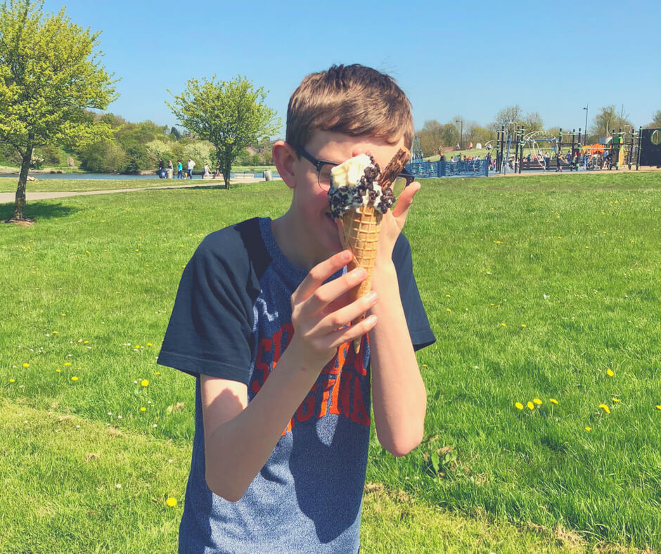 Teen boy holds an ice-cream in front of his face. He is walking. There is long grass and trees in the background. The sun is shining.