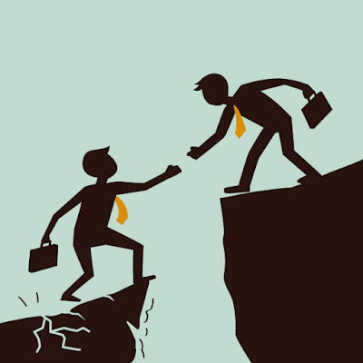 Silhouette of one businessman lending a hand to another over a chasm