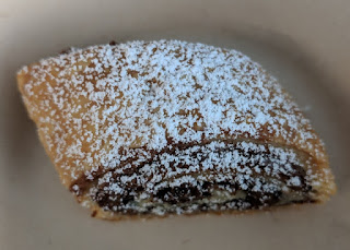 Piece of hazelnut/chocolate rugelach dusted with powdered sugar.