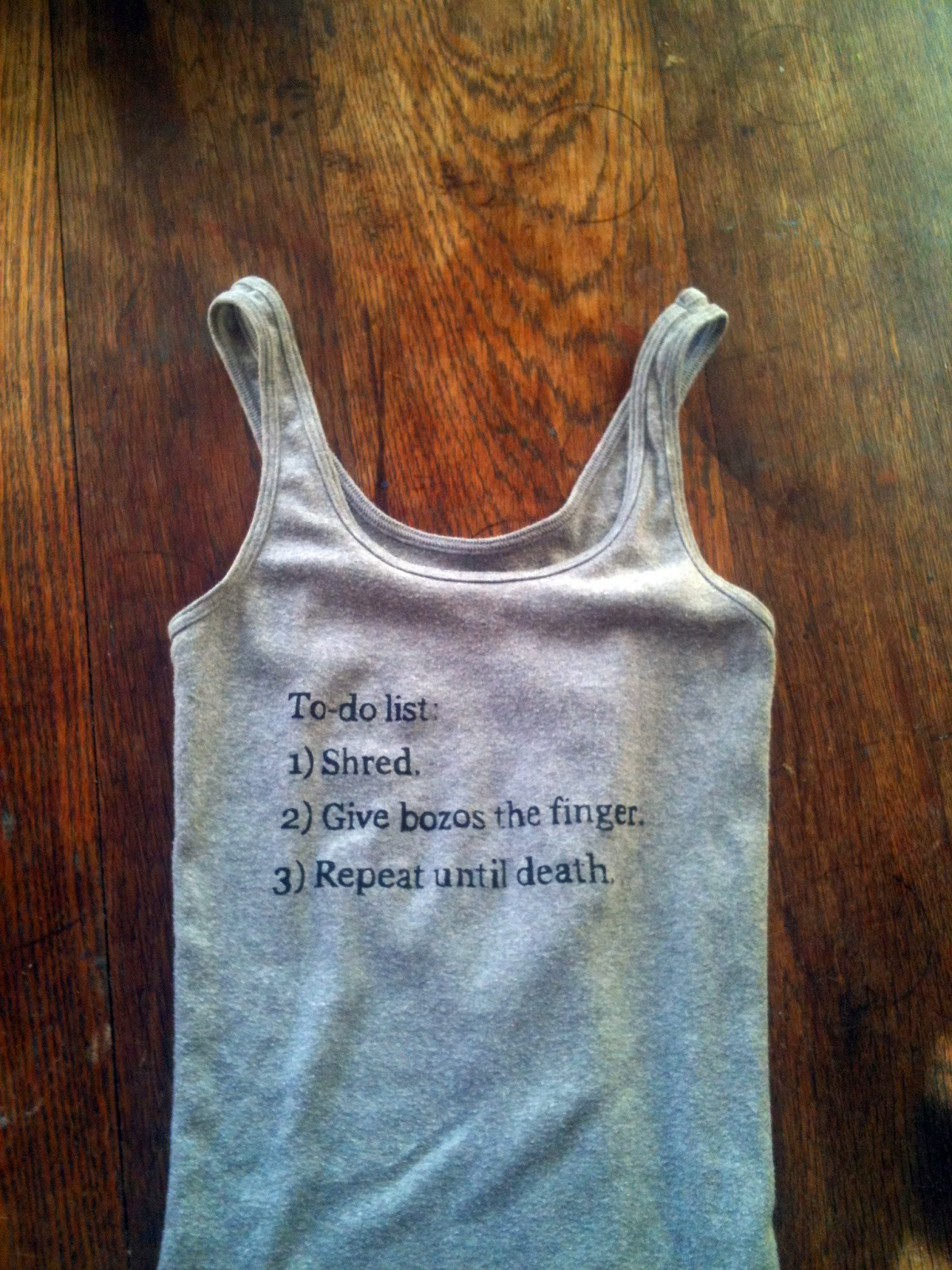 """Lindy West tweet on gray tank top: """"To-do list: 1) Shred 2) Give bozos the finger 3) Repeat until death."""