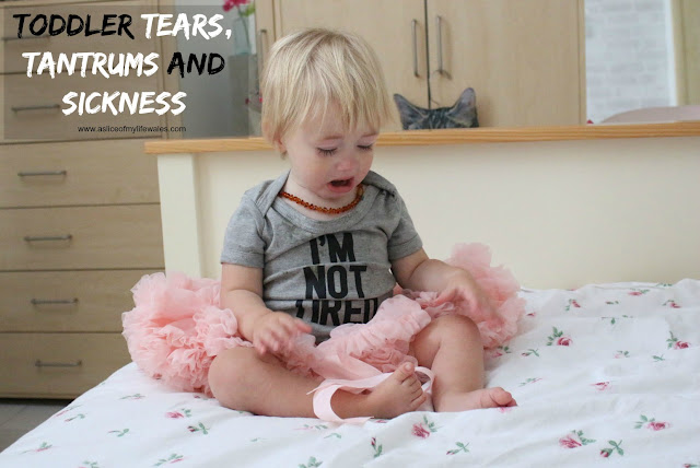toddler tears tantrums and sickness. crying baby sat on bed wearing i'm not tired vest and pink tutu