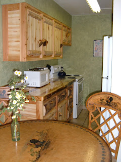 Kitchen with log cabinets, tile floor, faux green walls, table and chairs.