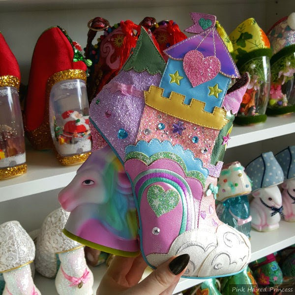 unicorn heeled pastel rainbow castle ankle boot in hand in front of shoe shelves