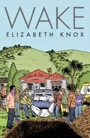 Cover of Wake, featuring an illustration of seven people of various genders and races lowering a long, wrapped bundle into a deep hole. Behind them, a blue truck holds several more wrapped bundles. A bungalow and a large hill are visible in the background.