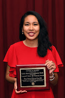 Dr. Nguyen-Tran smiles and holds her award plaque