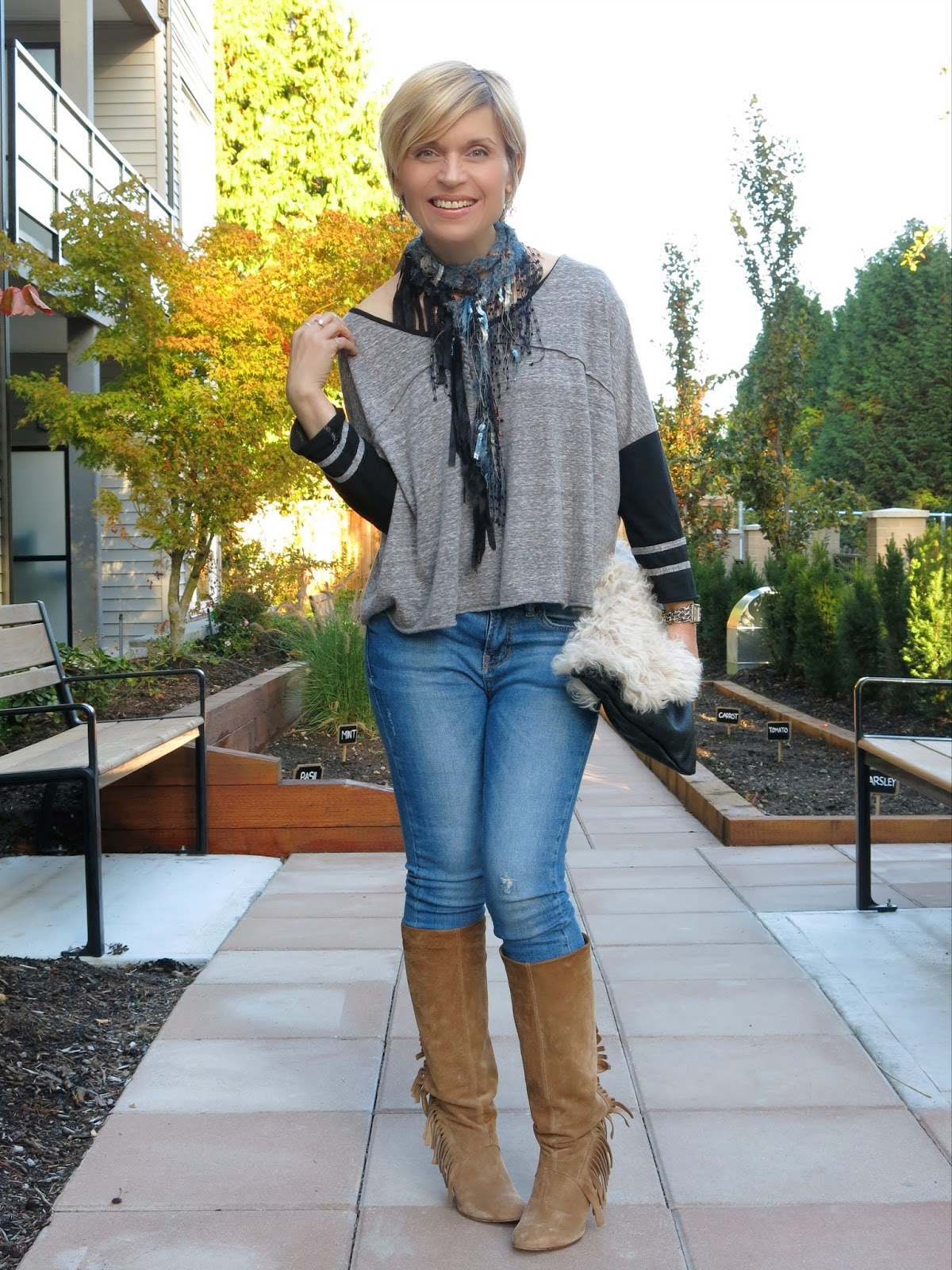 styling skinny jeans and a baseball-style tee with a sherpa clutch and fringy scarf and boots