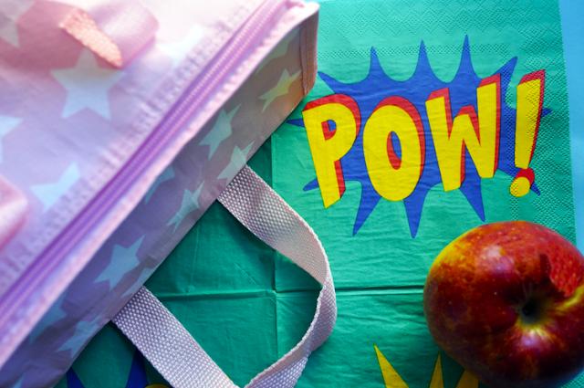se lee en letras de cómic pow! en una servilleta sale tambien una manzana y la mochila