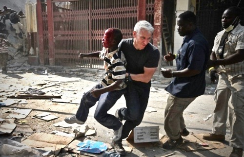 Anderson Cooper, covering the 2010 Haiti earthquake, rescues a boy in the middle of a looting incident. Strength and Dignity. marchmatron.com