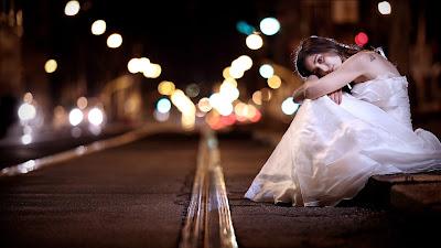 Chica vestida de blanco sentada en la calle mirando a cámara por la noche