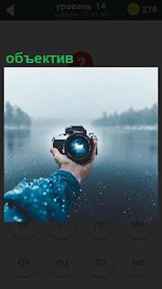 на фоне озера протянута рука для селфи, в которой обьектив фотоаппарата