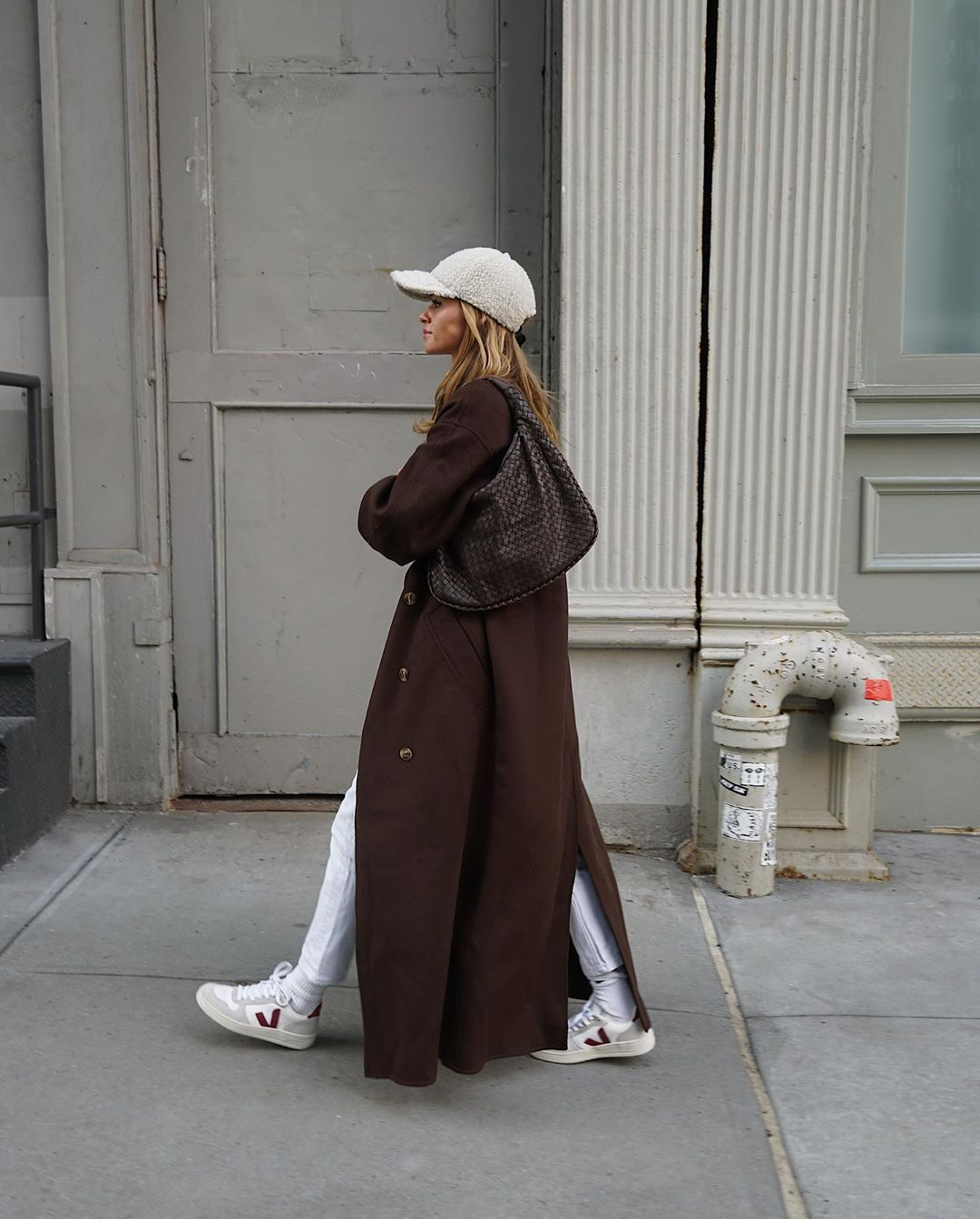 Casual-Cool Weekend Outfit — Shearling Hat, Long Brown Coat, Woven Hobo Bag, Cropped White Jeans, and Veja White Sneakers