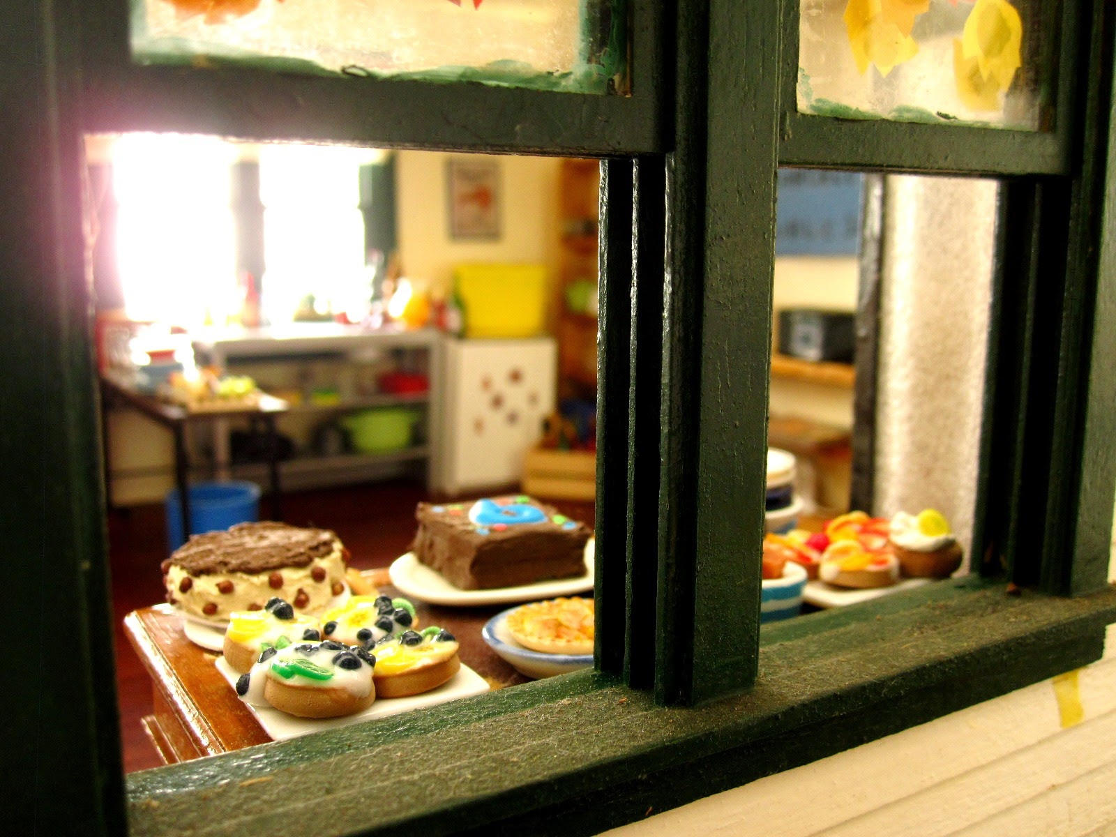 View from a miniature dolls' house veranda to inside where there is a table laden with cakes.