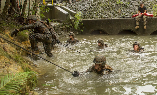 CAMP GONSALVES, OKINAWA, Japan - Marines and sailors use ropes to pull themselves across a stream during the jungle endurance course June 20 at Camp Gonsalves, Marine Corps Base Camp Smedley D. Butler, Marine Corps Installations Pacific. As part of the course, the service members are expected to navigate their way through water obstacles and pass through tunnels while holding onto a rope, allowing them to safely and effectively complete their training. The Marines and sailors are with 1st Battalion, 8th Marine Regiment, which is currently assigned to 4th Marines, 3rd Marine Division, III Marine Expeditionary Force, under the unit deployment program. (U.S. Marine Corps photo by Lance Cpl. Diamond N. Peden/Released)