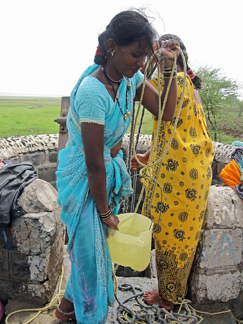 women drawing water from well