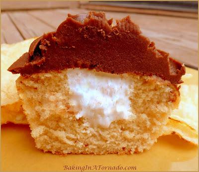 Fluffernutter Cupcakes, reminiscent of a favorite New England sandwich. A peanut butter cupcake with a marshmallow fluff center. Add a chocolate frosting, and you've got dessert. | Recipe developed by www.BakingInATornado.com | #recipe #cupcake