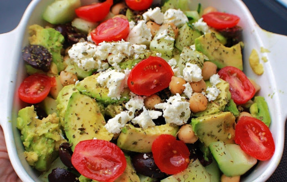 this is a summer salad with feta cheese, olives, avocado, grape tomatoes, cucumbers in a delicious homemade greek style dressing all inside a corning ware white dish