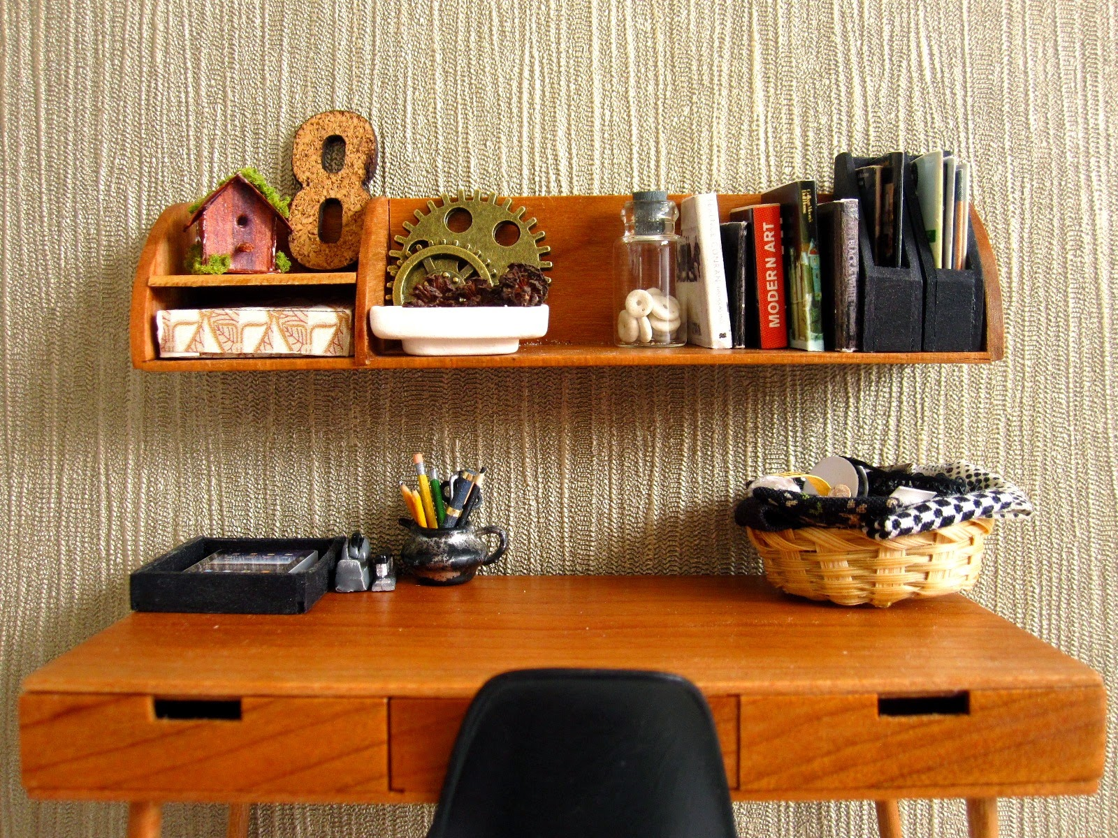 Modern dolls' house scene of a mid-century modern desk with shelf above holding a selection of books and magazines plus various industrial-style ornaments in browns and blacks,