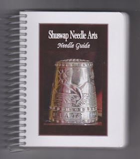 small spiral bound book with a silver thimble picture on the cover