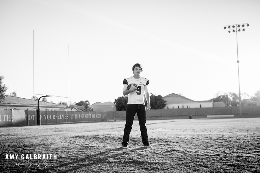 black and white image high school football player on the football field