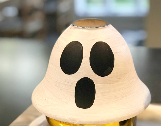 Add a spooky ghost face to an old repurposed lamp globe