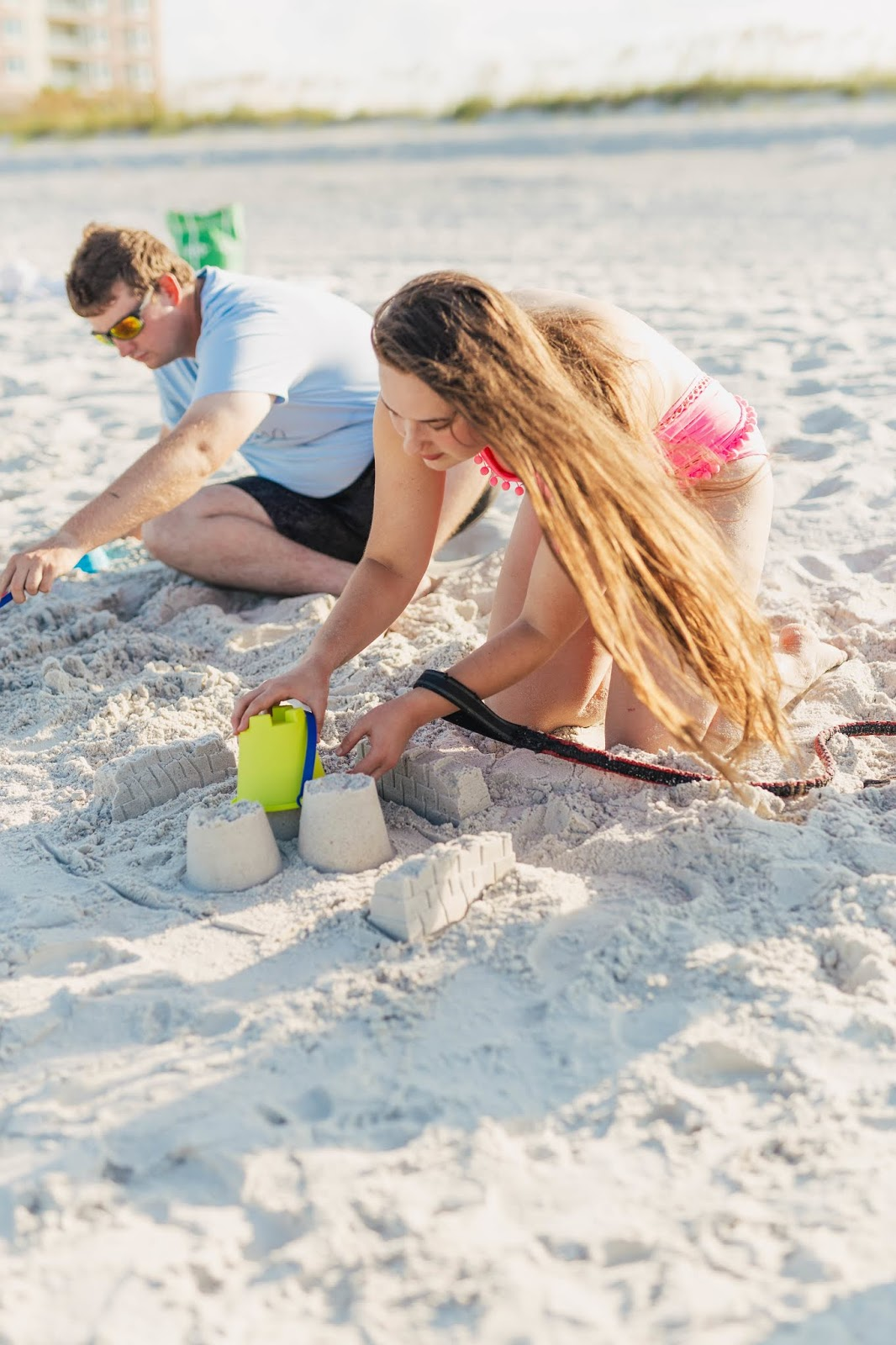 Girl in pink one-piece swimsuit with boyfriend and brindle dog at the beach with sand castle kit from target