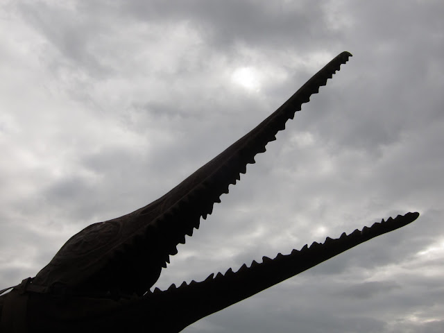 Jaws of metal torpedo sea-creature, Weymouth, Dorset, against cloudy sky