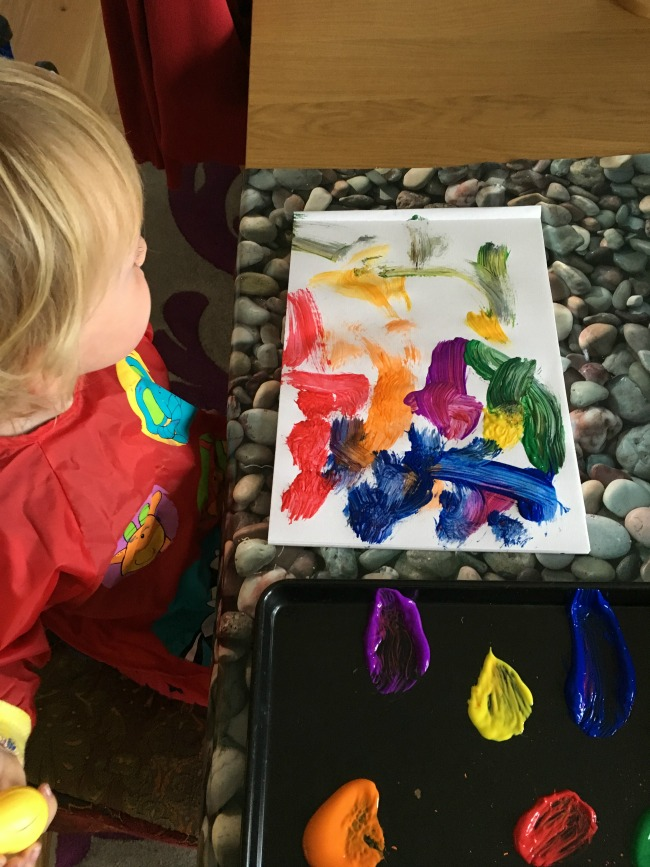 toddler-painting-sat-at-a-table