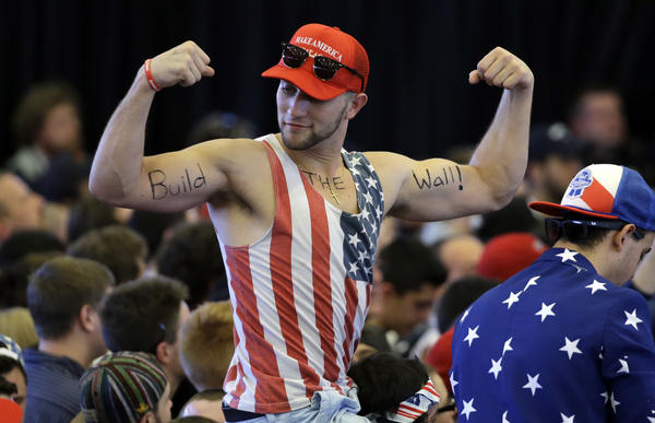 "Trump supporter flexes his muscles with the words ""Build The Wall"" written on his biceps"