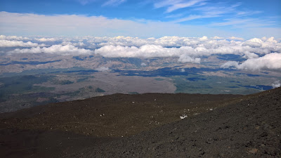 Clouds, lava and views from Mount Etna main crater.