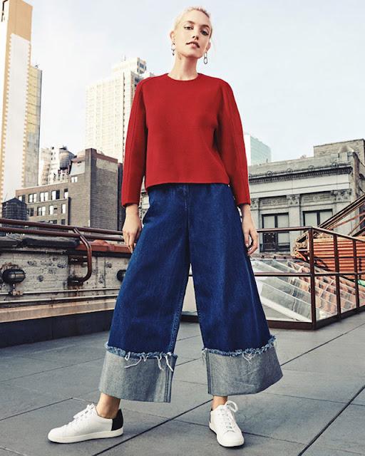 Девушка в красном свитере и широких джинсах