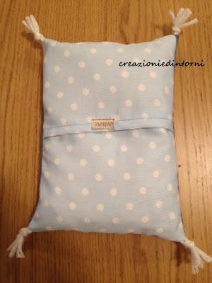 cuscino termico azzurro a pois  bianchi e nappine in lana