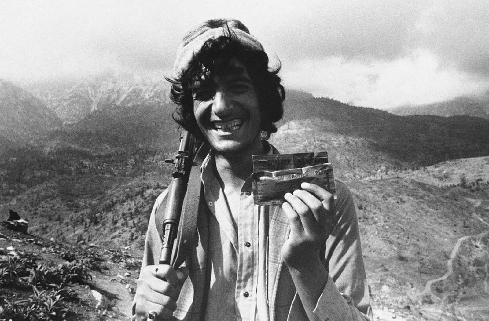 A Muslim guerrilla in Afghanistan's Paktia Province shows off his combat ration of peanut butter from the United States, on July 11, 1986. Many of his fellow guerrillas battling the Soviet-backed Communist government don't like the American food and had been throwing it away.
