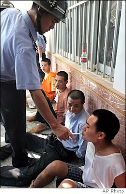 A Chinese police officer lights an inmate's last cigarette minutes before his execution.