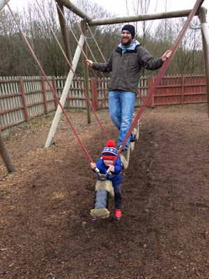 Little boy and Daddy on a rope walk swing