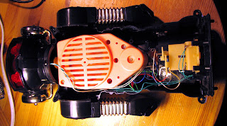 [Image: The robot opened up. A bunch of wires go from inside its head down to where its feet are, where some gears can also be seen. In the middle, a big pink box with a speaker in the front.]