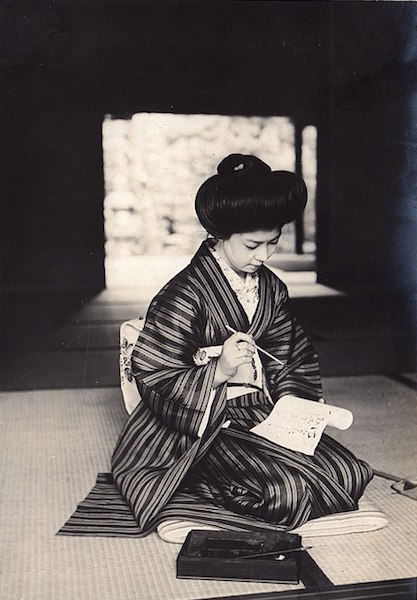 Photo from 1911 of a Japanese woman in a kimono writing on a paper roll, by Elstner Hilton