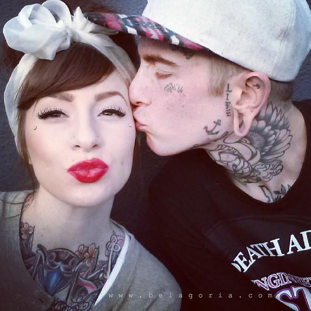 vemos a un chico tatuado besando a una chica tatuada