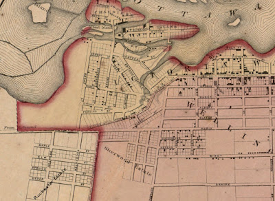 Crop of a map from 1863 which shows Ottawa with limits at Bank Street (East), Centre Street (now Somerset, South), City Limits (Now City Centre Ave, West), and the Ottawa River (North), with city boundaries and wards indicated by colouring. Wellington Street and its extensions George St and Victoria Terrace, have a dotted line indicating the boundary between Victoria Ward (north of the line) and Wellington Ward (south of the line). The streets and individual lots (where blocks have been subdivided) are shown, and black squares indicating the location of buildings are on about a third of them. Between Bay and Concession Line (now Bronson), Wellington Street makes an abrupt turn southwest and is labelled George St which heads to the east approach to Pooley's Bridge (which is neither drawn nor marked) and continues to Hill Street (not labelled, now Brickhill) after which it becomes Victoria Terrace where it meets Richmond Road at a shallow angle on the southern boundary of LeBreton Flats. Richmond Road is drawn as continuous in line with Maria Street (now Richmond). North of the extension of Maria Street (Laurier), nothing is drawn west of Broad Street inside or outside city limits, aside from a label