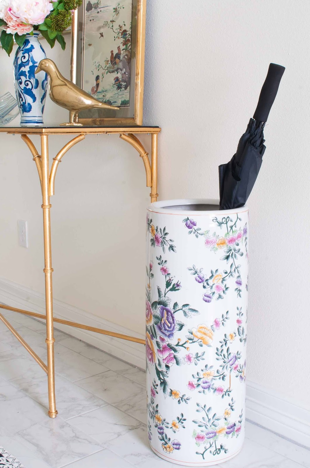 A colorful vintage floral umbrella stand next to a gold console table in a foyer.