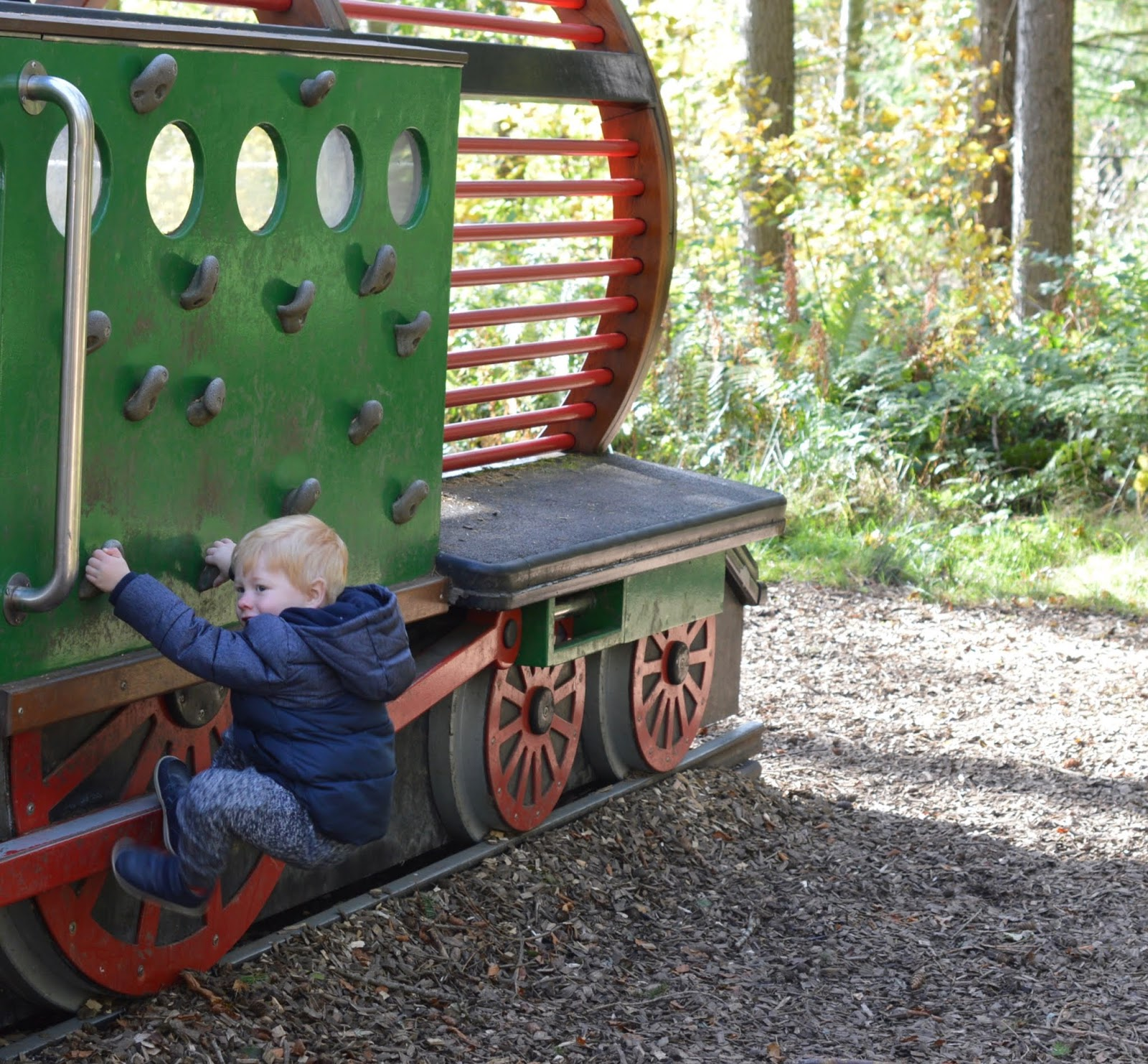 Visiting the Adventure Playground & Outdoor Play Areas at Wallington Hall  - toddler climbing on train