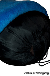 Cramer Imaging's photograph of a sleeping bag stuffed in its sack with a blue blanket on top